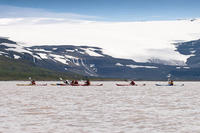 Kayaking under the magnificent Drangajokull glacier.
